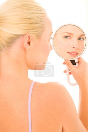 Photo pour Femme qui regarde dans le miroir en fond blanc - image libre de droit