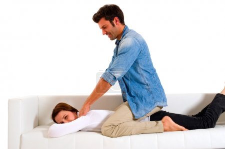 Photo for Man massaging the shoulders of a woman in a white background - Royalty Free Image