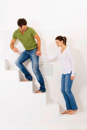 Photo pour Couple dans les escaliers tenant la main dans un fond blanc - image libre de droit