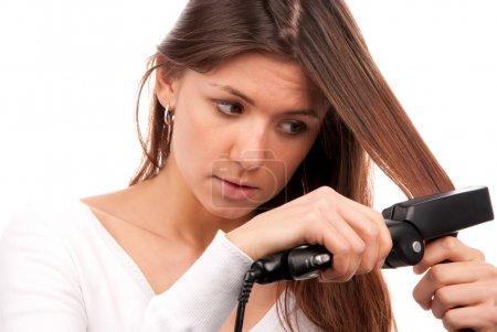 Photo pour Jeune femme brune utilisant des lisseurs de cheveux noir fer plat pour faire nouvelle coiffure élégante isolé sur un fond blanc - image libre de droit