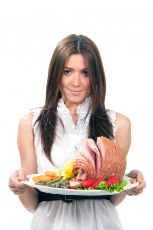 Woman hold plate baked honey sliced ham