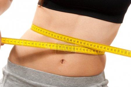 Photo pour Femme ajustement athlétique mince mesure sa taille avec ruban métrique jaune après un régime isolé sur fond blanc - image libre de droit