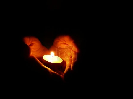 Photo for Heart-shaped hands holding one candle in darkness - Royalty Free Image