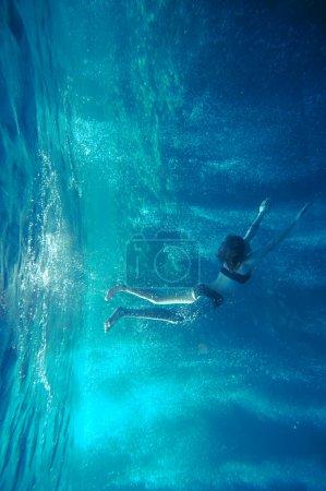 Photo pour Fille Freediving avec bulles d'air et coraux, et surface de l'eau - image libre de droit
