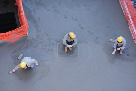 Photo for Three workers with one smoothing out freshly poured concrete. - Royalty Free Image