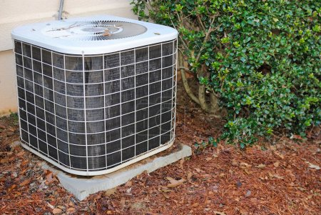 Photo for Residential air condition unit in mulch near a home. - Royalty Free Image