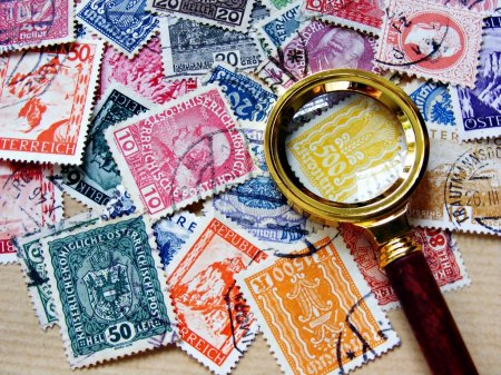 Photo for A collection of used Austrian stamps with a small elegant magnifying glass - Royalty Free Image