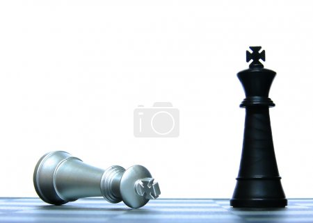 Photo for Victorious black king and Defeated white king in a chess game conceptually depicting defeat and victory - Royalty Free Image