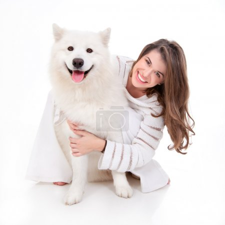 Photo for A studio image of a young woman, dressed in white, with her white dog, huging it, both posing, looking happy and smiling - Royalty Free Image