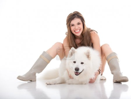 Young woman holding her white dog in front of her
