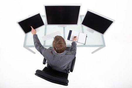 Photo pour Homme d'affaires dans son bureau de haute technologie propre regardant sur les moniteurs vue supérieure - image libre de droit