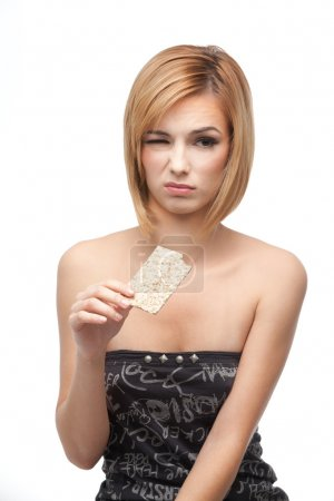 Young woman tasting healthy bread and hating it
