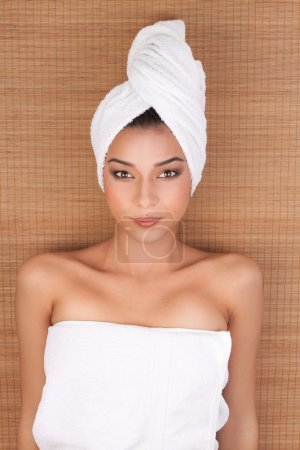Portrait of a young woman at a day spa, with towels around her b