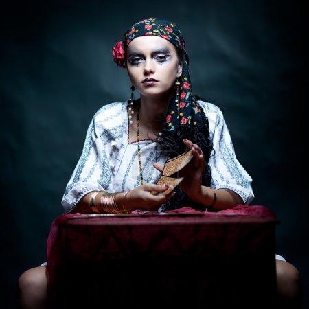 Foto de Un retrato de una Pitonisa gitana, sentado en una mesa y mezclar las cartas del tarot que tiene en sus manos. Ella está mirando a la cámara - Imagen libre de derechos