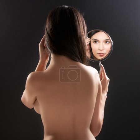 Photo for A beauty studio picture of a young woman looking in a mirror, while her back is turned to the camera. the mirror held over her left shoulder reflects her smilin - Royalty Free Image