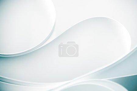 Photo pour Une macro, abstraite, image de fond d'une feuille de papier torsadée blanche, en cercle, forme incurvée, sur fond bleu - image libre de droit