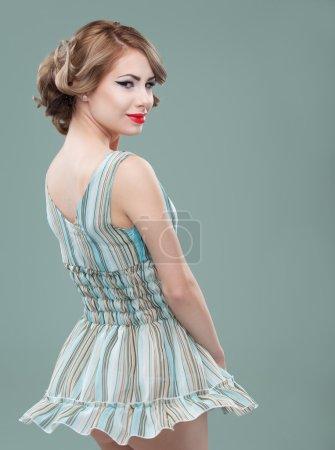 Beauty portrait of young woman wearing a mini dress, twirling, s