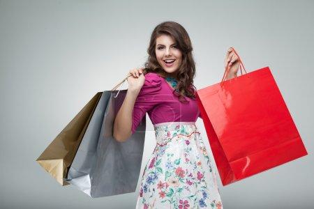 Photo pour Portrait d'une belle jeune femme, dans une tenue colorée, tenant dans ses mains quelques sacs à provisions en studio. elle est de rire et de la recherche très heureux. - image libre de droit