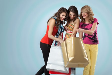 Studio image three beautiful young women holding shopping bags l