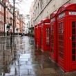 Row of phone booths in rainy London. Street view....