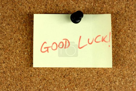 Photo for Yellow small sticky note on an office cork bulletin board. Good luck wishes. - Royalty Free Image