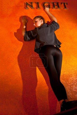 Photo pour Femme se trouve un air de défi s'appuyant sur un mur avec une nuit de signe - image libre de droit