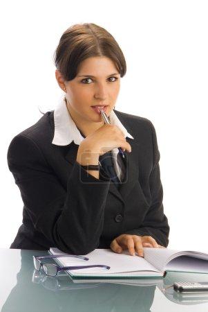 Photo pour Une jeune femme en manteau noir et chemise blanche et une cravate, assis derrière une table de bureau et de jouer avec des lunettes - image libre de droit