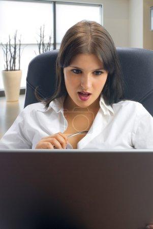 Photo pour Un travailleur de cols blancs s'habiller d'une chemise blanche, assis sur un fauteuil, travaillant avec un ordinateur avec un ciao l'écran de veille qui vous pouvez décoller facilement - image libre de droit