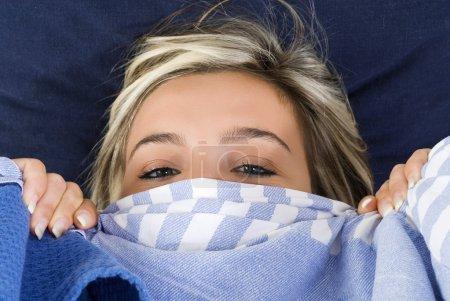 Photo pour Blonde et mignonne fille jouant avec une feuille bleue sur son lit et faire face - image libre de droit