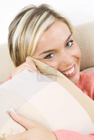 Photo pour Portrait d'une jolie femme blonde portant une robe rose du soir assise sur un canapé avec des tresses et armant un oreiller - image libre de droit