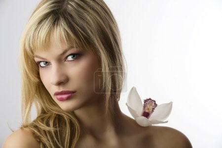 Photo for Beauty portrait of young blond woman with orchid near face - Royalty Free Image