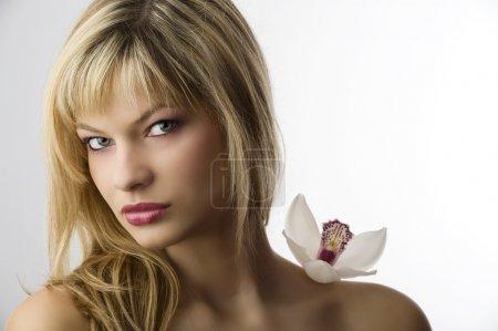 Photo pour Portrait de la beauté de la jeune femme blonde avec orchidée près de face - image libre de droit