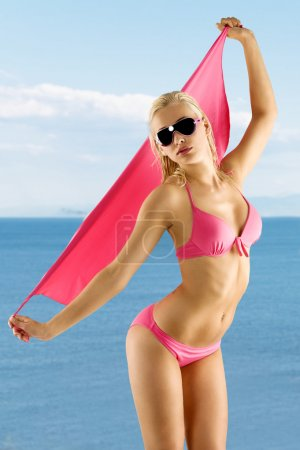Blond sexy girl in pink bikini and sunglasses
