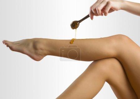 Photo pour Femme mettre de la cire dépilatoire sur sa jambe comme du miel - image libre de droit