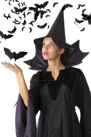 Photo pour Sorcière avec robe noire et chapeau ayant chauve-souris noire tout autour - image libre de droit