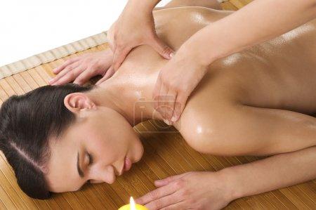 Photo pour Jolie belle femme caucasienne couchée et recevant un massage avec de l'huile sur bois tapis - image libre de droit