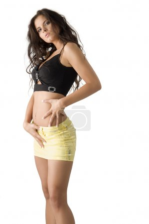 Photo for Sensual brunette with short yellow skirt and a black top taking pose - Royalty Free Image