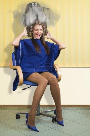 Photo pour Jeune femme sous un sèche-cheveux brûlant la tête dans la fumée - image libre de droit