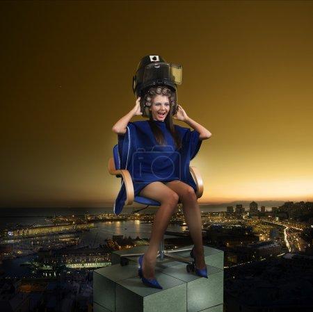 Photo pour Une fille criant sous un sèche-cheveux mis sur un dessus et tombant dans une ville - image libre de droit
