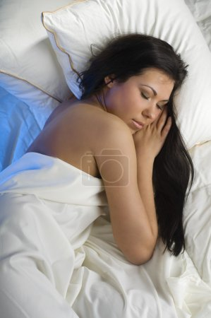 Photo for Young and beautiful brunette in a bed sleeping between pillow - Royalty Free Image