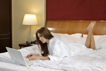 Brunette woman looking at a laptop lying on bed at home