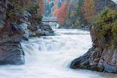 Muddy Waterfall on Autumn Mountain River
