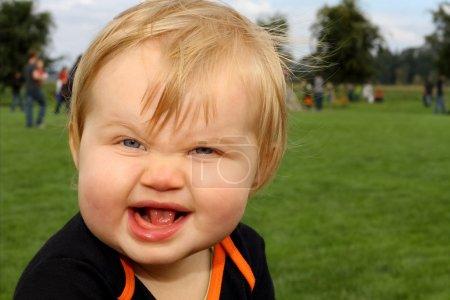 Photo pour Adorable blond aux yeux bleus bébé fille rend étrange mais mignon et drôle expression faciale à la caméra . - image libre de droit