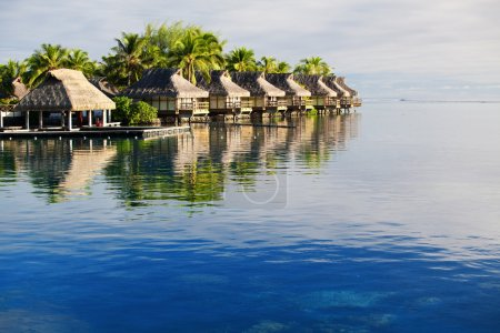 Amazing tropical resort with huts over blue water