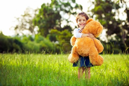 Little cute girl standing in the grass holding teddy bear