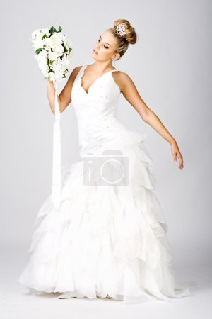 Happy young bride with bouquet on white
