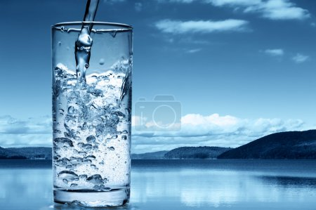 Photo for Pouring water into a glass against the nature background - Royalty Free Image