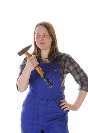 Photo pour Jeune femme (Erin Crafts, bricoleur, stagiaire) aux longs cheveux blonds portant une chemise à carreaux et une salopette bleue et tenant un gros marteau - image libre de droit