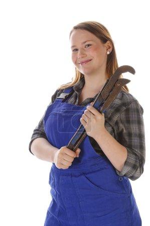Photo pour Jeune femme (Erin Crafts, bricoleuse, stagiaire) aux longs cheveux blonds portant une chemise à carreaux et une salopette de travail bleue. Elle tient un gros plombier. - image libre de droit