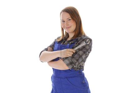 Photo pour Jeune femme (Erin Crafts, bricoleuse, stagiaire) aux longs cheveux blonds portant une chemise à carreaux et une salopette de travail bleue. Elle tient une clé. - image libre de droit